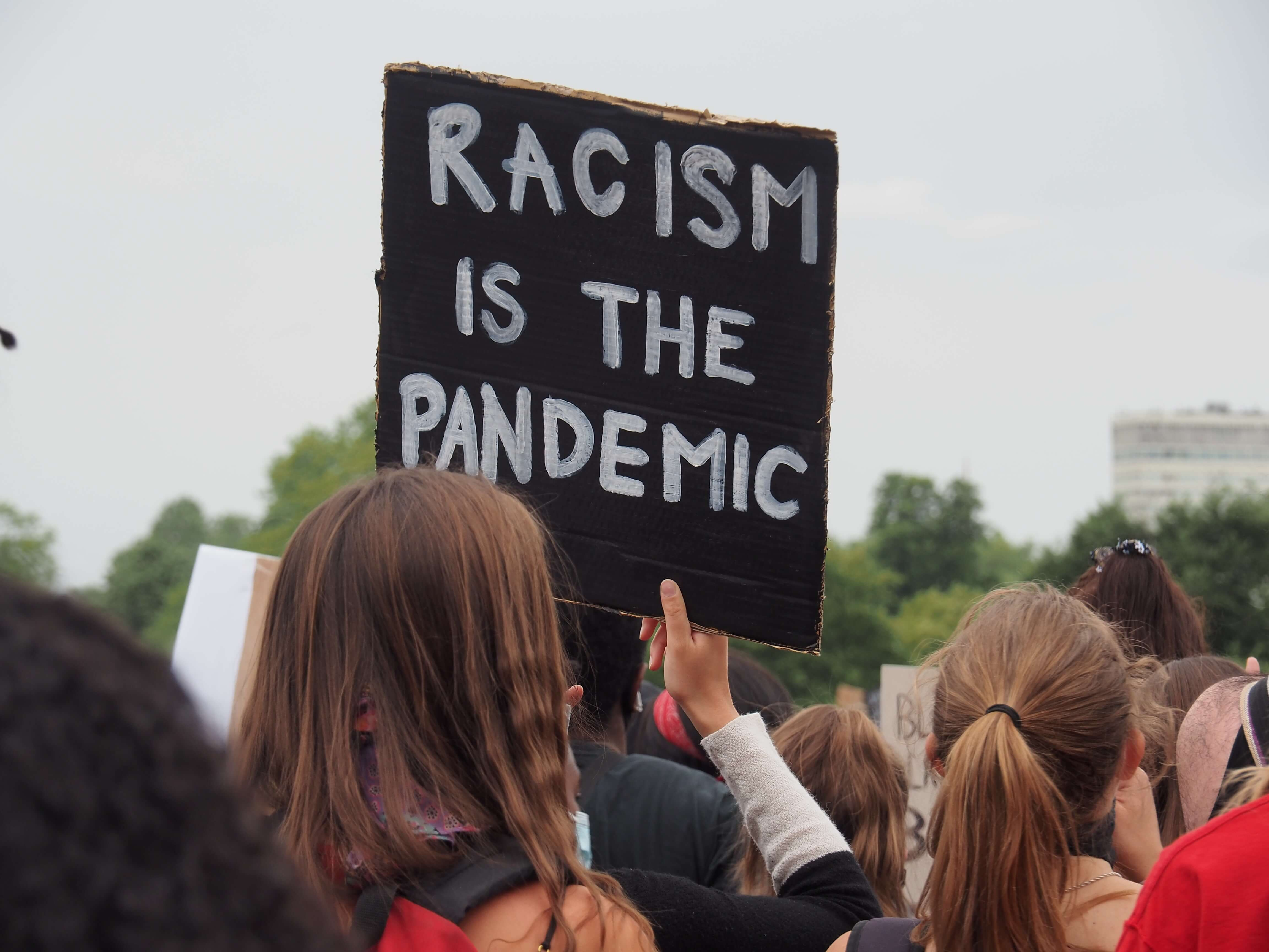 Photo of protest sign saying Racism Is the Pandemic